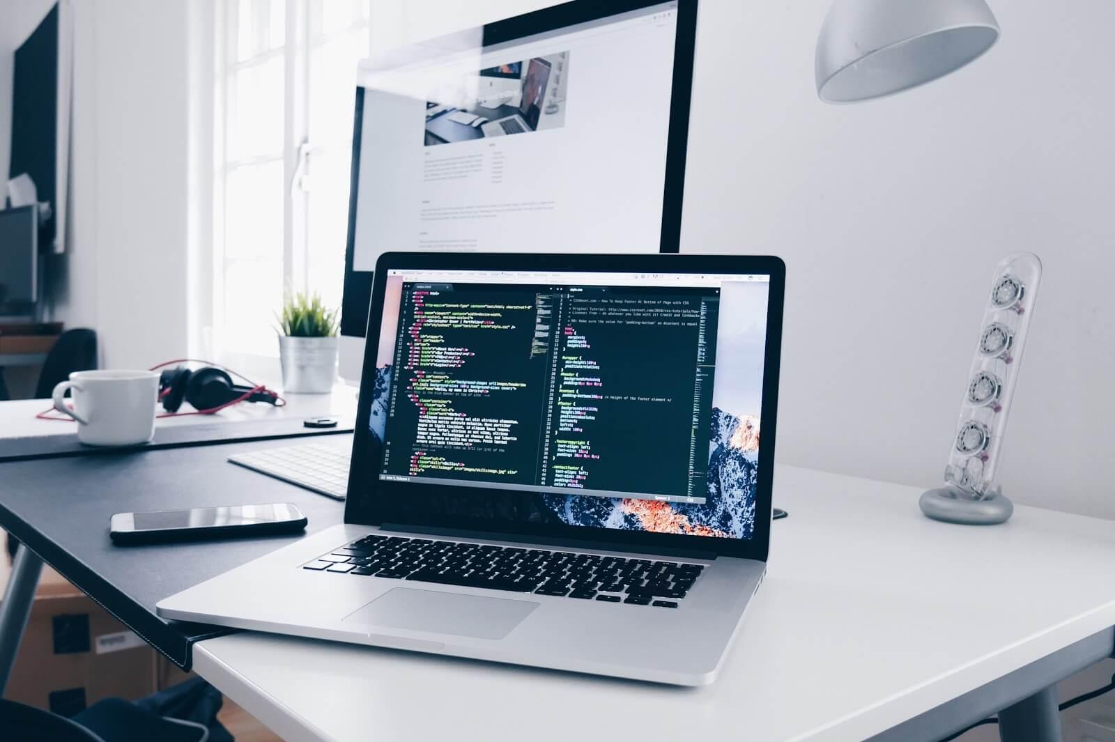 Computador em cima de uma mesa branca com código de programação aberto. Em cima da mesa há um monitor grande, fones de ouvido, xícara de café, vasinho, luminárias e celular. Ao fundo uma janela deixando a claridade entrar no ambiente. (Foto: Christopher Gower)