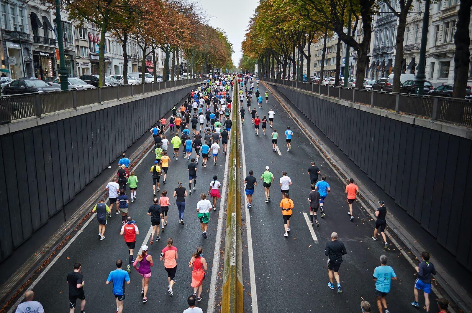 Corrida de rua em duas avenidas na Bélgica, com várias pessoas correndo na mesma direção, saindo de um túnel com árvores e carros nas ruas paralelas (Foto: Mārtiņš Zemlickis)