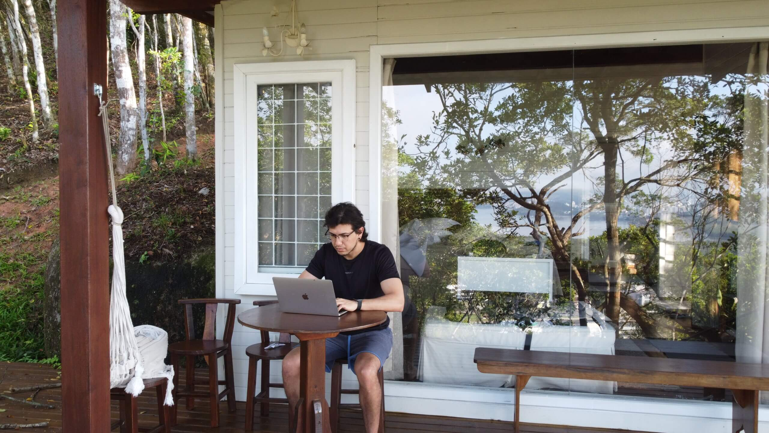 Douglas Fernandes como Nômade Digital, trabalhando com um notebook em frente a uma varanda.