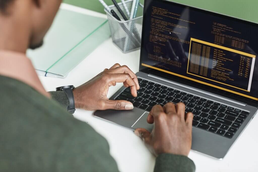 """Pessoa preta trabalhando em um notebook em que é possível ver um trecho código. Capa do artigo """"Fases de testes e Tipos de testes""""."""