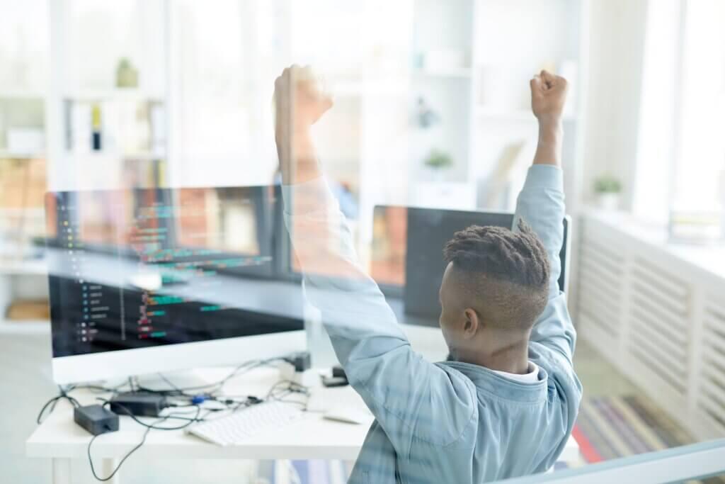 Homem preto comemorando na frente de um computador com códigos.