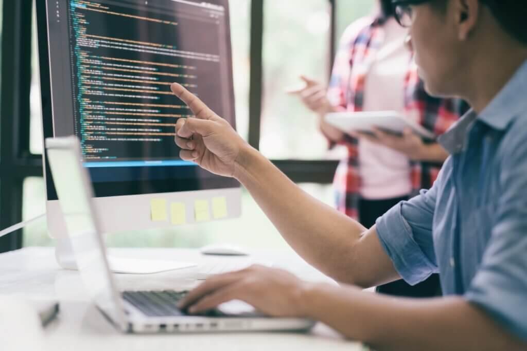 Capa do artigo sobre Spring Actuator que mostra um time de desenvolvimento de software composto por um homem sentado ao computador e uma mulher em pé.