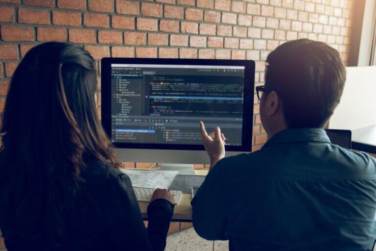 """capa do artigo """"Design de código seu papel até hoje"""" cm duas pessoas, um homem e uma mulher, analisando o mesmo monitor com código."""