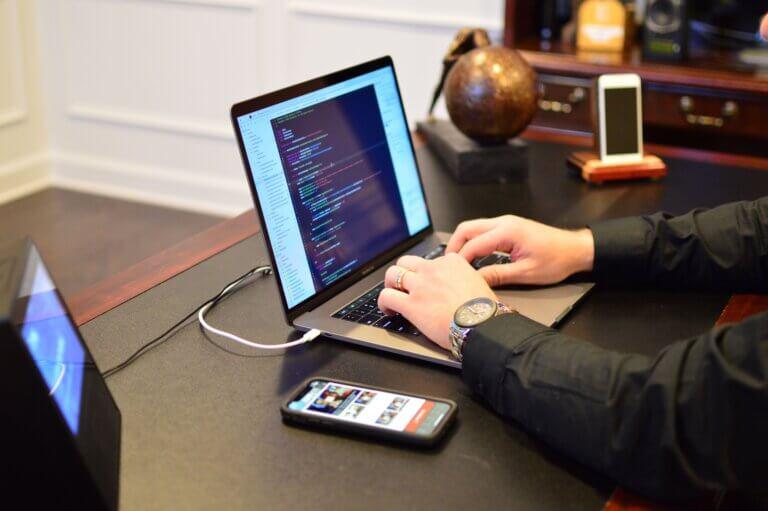 Capa do artigo sobre Plugins do Beagleque mostra uma pessoa branca codando em um laptop com 2 celulares e um tablet ao lado.