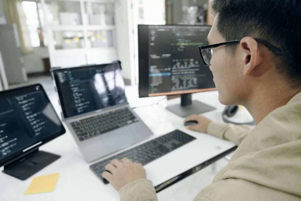 capa do artigo o que é gRPC e como usá-lo no Beagle que mostra um programador homem desenvolvendo com três telas.