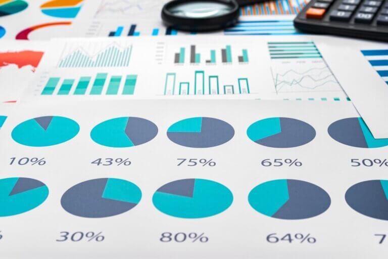 Capa do artigo sobre a Stack Overflow survey 2021 com gráficos impressos em folhas espalhados em uma mesa