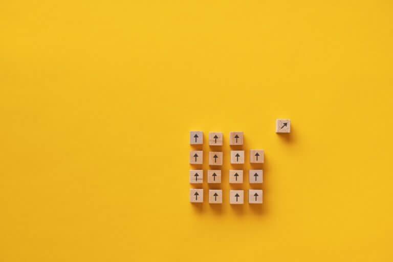 Capa do artigo Transição de carreira para tecnologia em que quadrados de madeira aparecem em um fundo amarelo enquanto um desses quadrados está mudando de rota.