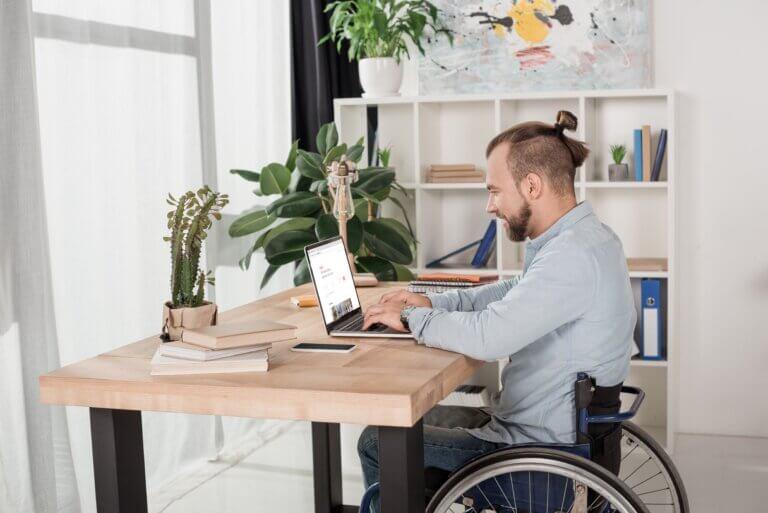 """Capa do artigo """"termo PCD e inclusão no mercado de trabalho"""" com um homem branco de perfil em uma cadeira de rodas enquanto usa um notebook."""