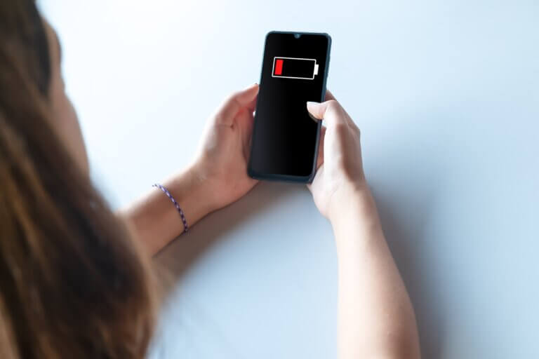 """Capa do artigo """"Aprendizado de máquina para reduzir consumo de energia em smartphones"""" que mostra uma mulher branca de cabelos longos com um smartphone nas mãos onde é possível ver que ele está com a bateria acabando."""