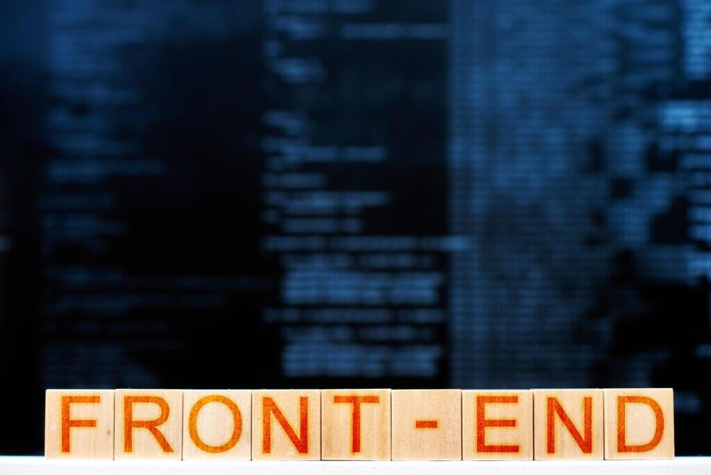 """Capa do Artigo desenvolvimento front-end onde se lê a palavra """"front-end"""" escrita em um quadrado de madeira e letras vermelhas, atrás há códigos de programação embaçados."""