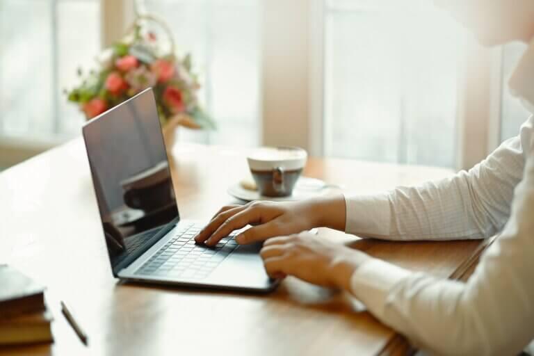 """Capa do artigo """"Como manipular outputs no Github Actions"""" que mostra um homem de camisa branca trabalhando de um notebook em uma mesa, ao fundo vemos uma xícara de café e um vaso de flores."""
