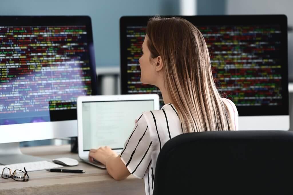 """Capa do artigo """"Workflows no GitHub Actions"""" com uma mulher programando usando três telas."""