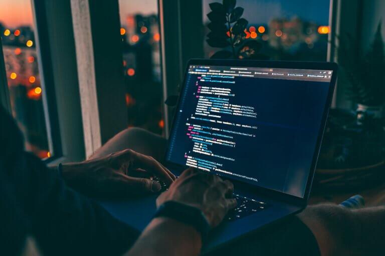 Capa artigo Fluent API cm uma pessoa trabalhando de um notebook em que se vê um código de programação na tela, isso durante o entardecer.