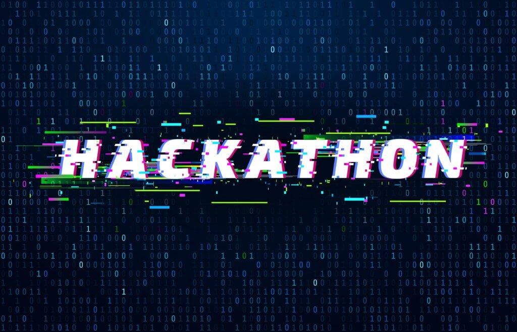 """Capa do artigo com a a palavra """"hackathon"""" escrita em branco em um fundo escuro com detalhes pequenos e coloridos."""