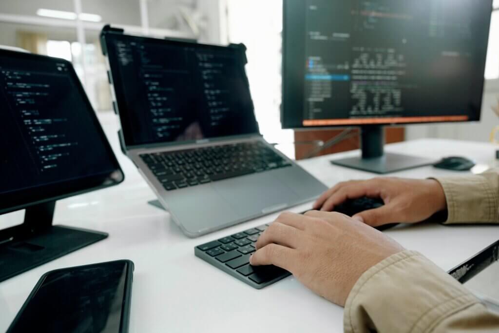 Capa do artigo sobre reflectionless que mostra um par de mãos brancas programando com três telas.