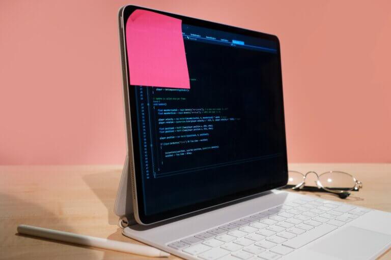 Capa do artigo Clean Architecture onde se vê um notebook com um codigo desfocado e um post it em rosa. Ao lado, na mesa temos uma caneta branca e um óculos.