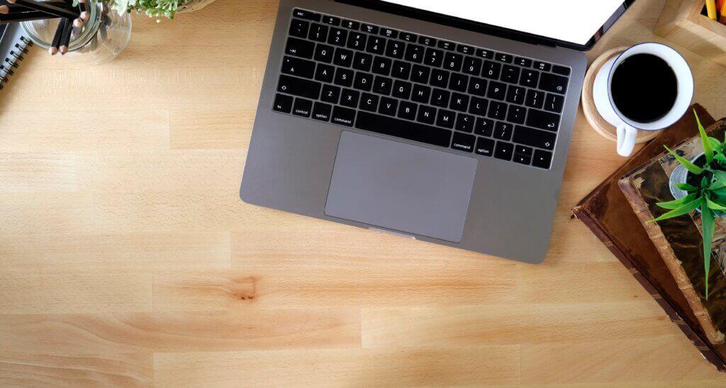 Capa do artigo sobre a ferramenta kind, usada para criar clusters locais no kubernetes. Na imagem se vê o teclado de um notebook em uma mesa de madeira e uma xícara de café ao lado.